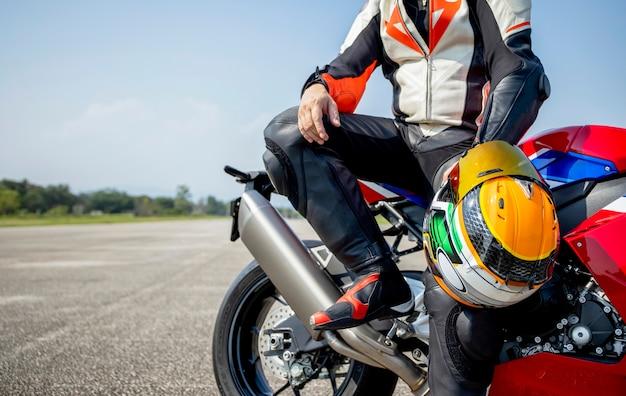 Fahrermotorrad, das seinen motorradhelm auf einem großen fahrrad im straßenreiten hält