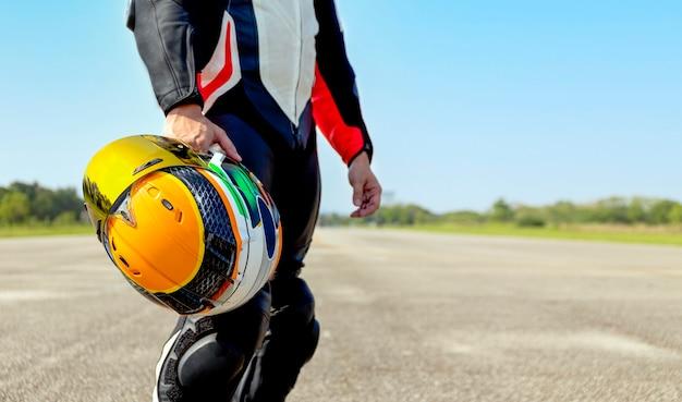 Fahrermotorrad, das seinen motorradhelm beim straßenreiten hält