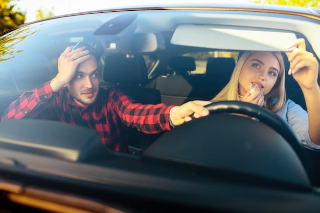 Fahrlehrer fährt das auto, während die frau make-up aufträgt, fahrschule. mann, der dame unterrichtet. führerscheinausbildung