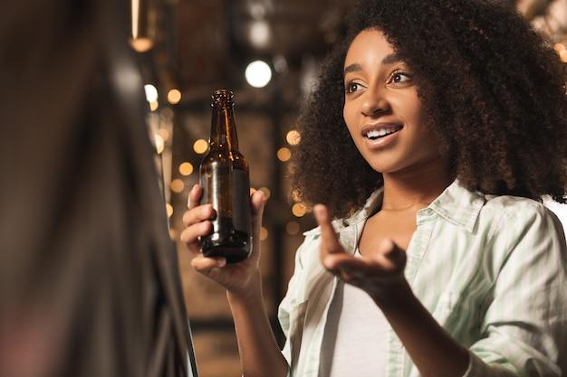 Fahrpunkt nach hause. schöne lockige frau, die mit barmann plaudert und ihren standpunkt beweist, während sie an der bar sitzt und bier trinkt