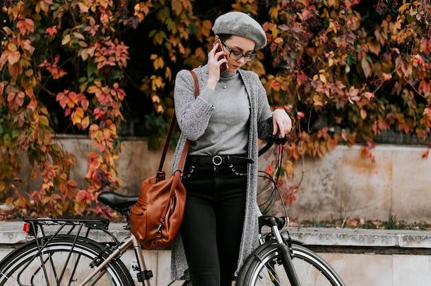 Fahrrad alternativer transport und frau, die am telefon spricht