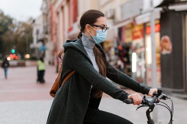 Fahrrad alternativer transport und frau, die maske trägt