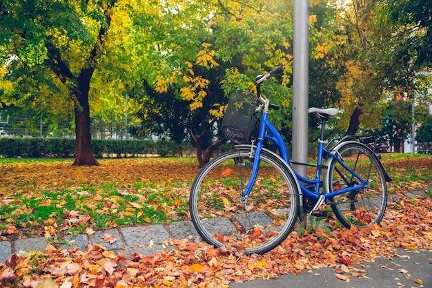 Fahrrad an einer säule im wiener park im herbst befestigt, gelbe blätter auf dem boden