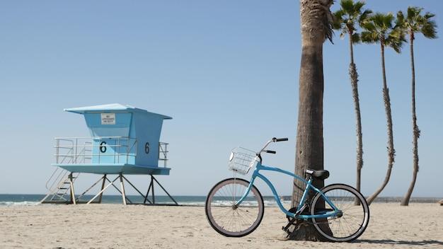 Fahrrad cruiser fahrrad von ocean beach, kalifornische küste usa. sommerzyklus, bademeisterhütte und palme