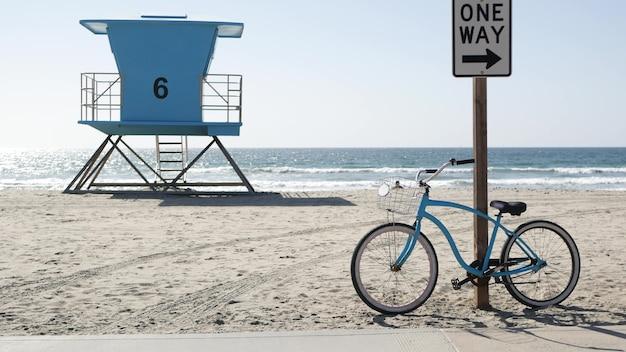 Fahrrad cruiser fahrrad von ocean beach, kalifornische küste usa. sommerzyklus, rettungsschwimmerturm, verkehrsschild