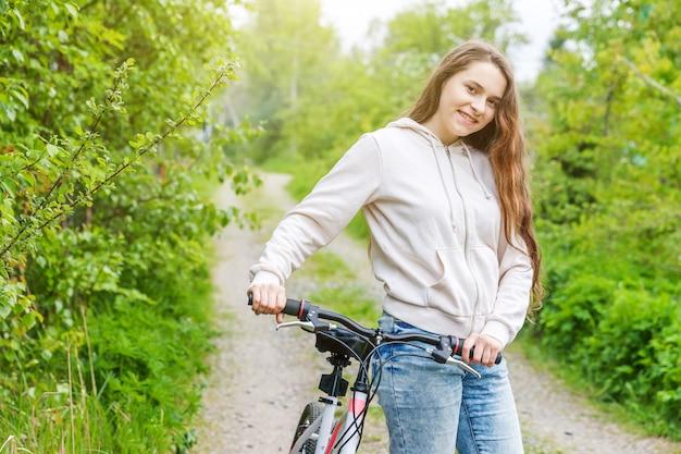 Fahrrad der jungen frau reitin einem stadtpark