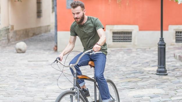 Fahrrad des jungen mannes reitauf plasterung