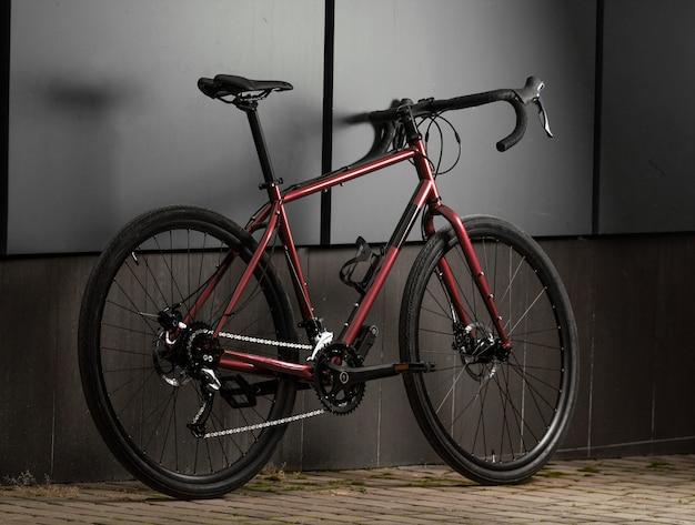 Fahrrad für den tourismus. rotes glänzendes rennrad auf grauer wand