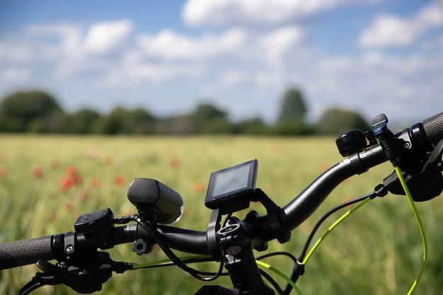 Fahrrad mit navigationsgerät. frühlingsfeld mit roten mohnblumen.