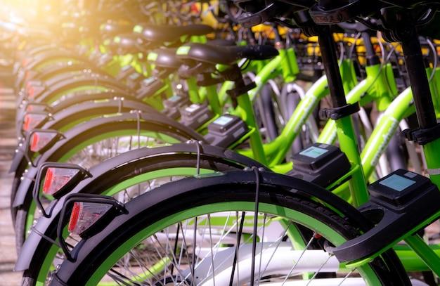 Fahrrad-sharing-systeme. fahrrad zu vermieten. fahrrad für stadtrundfahrt am fahrradparkplatz. umweltfreundlicher transport. öffentlicher verkehr der städtischen wirtschaft. fahrradstation im park. gesunder lebensstil.