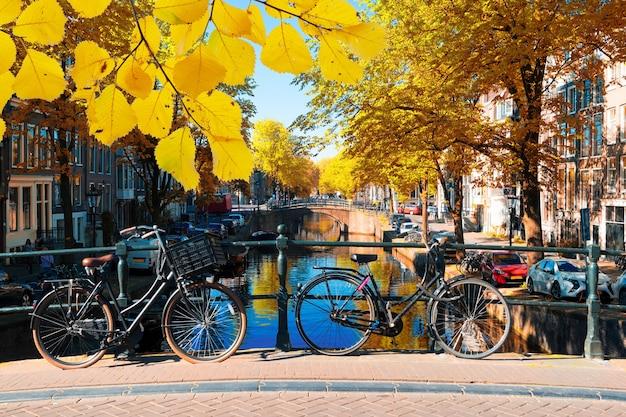 Fahrrad steht neben dem kanal in amsterdam, fällt in die niederlande