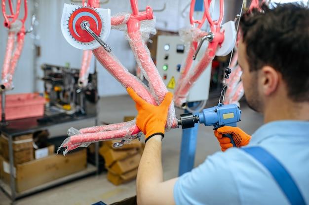 Fahrradfabrik, arbeiter hält rosa kinderfahrrad. männlicher mechaniker in uniform installiert fahrradteile, montagelinie in werkstatt