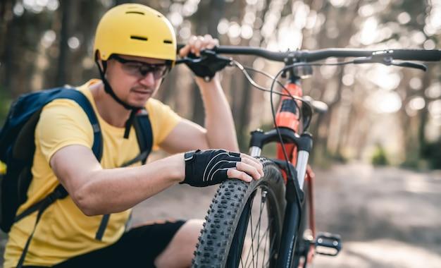 Fahrradfahrer, der den reifendruck des fahrrads vor der fahrt im wald überprüft