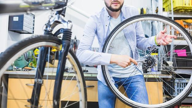 Fahrradmechaniker, der fahrradreifen mit schlüssel repariert