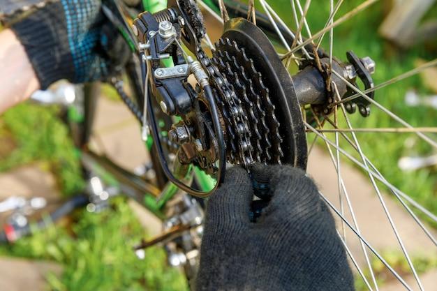Fahrradmechaniker repariert fahrrad in fahrradwerkstatt, im freien. hand des radfahrers fahrradfahrer untersucht, repariert modernes fahrradübertragungssystem. fahrradwartung, sportgeschäftskonzept.
