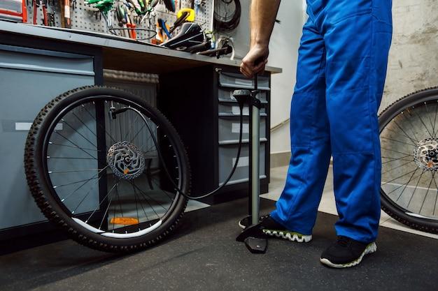 Fahrradmontage in der werkstatt, mann bläst das rad auf
