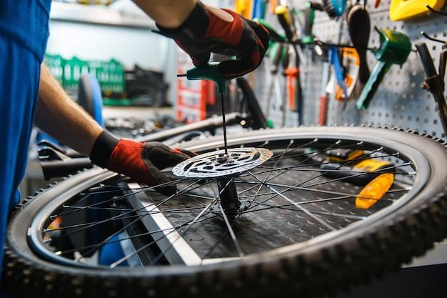 Fahrradmontage in werkstatt, mann installiert bremsscheibe