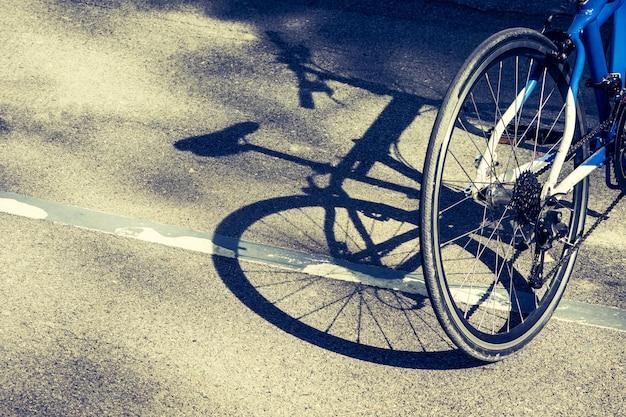Fahrradrad und -schatten auf fahrradweg in einem park.