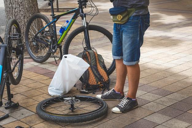 Fahrradreparatur. ein mann repariert ein fahrradrad auf der straße.