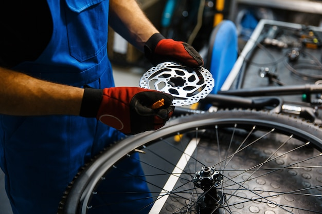 Fahrradreparatur in der werkstatt, mann, der bremsscheibe repariert