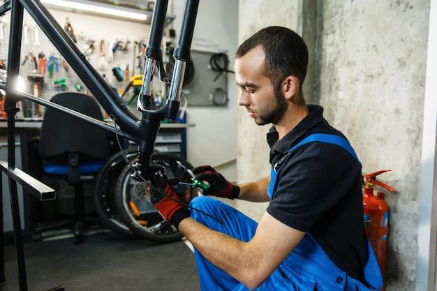 Fahrradreparatur in der werkstatt, mann, der kurbel repariert