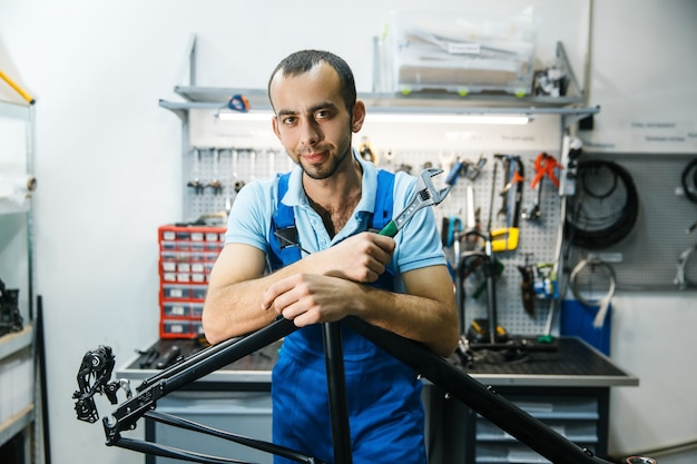 Fahrradreparatur in der werkstatt, mann posiert am rahmen