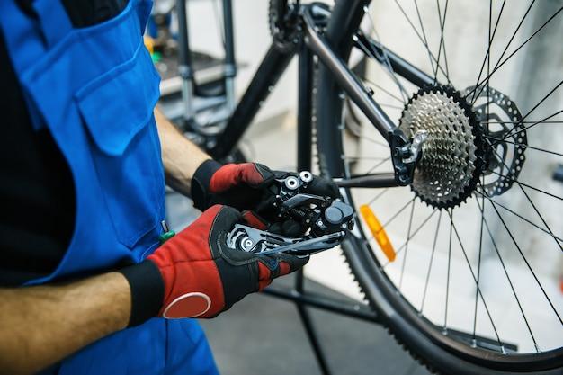 Fahrradreparaturwerkstatt, mann stellt den geschwindigkeitsschalter ein