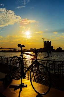 Fahrradschattenbildsonnenuntergang in Bangkok- und Chopraya-Fluss, Thailand