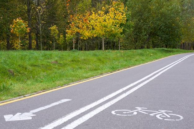 Fahrradschilder auf einem radweg in einem stadtpark.