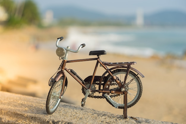 Fahrradtransportspielzeug auf sandseestrand im abendsonnenunterganghimmel