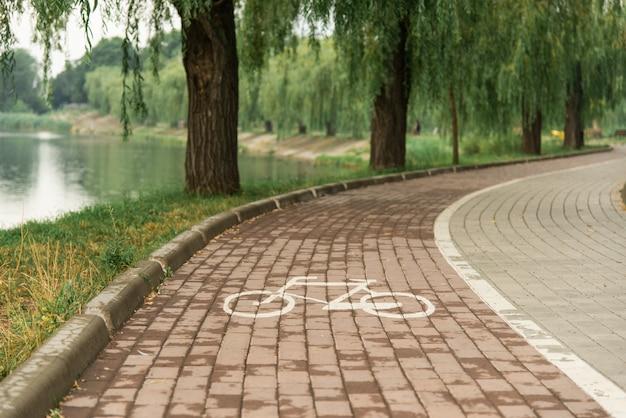 Fahrradweg im park nahe dem teich.