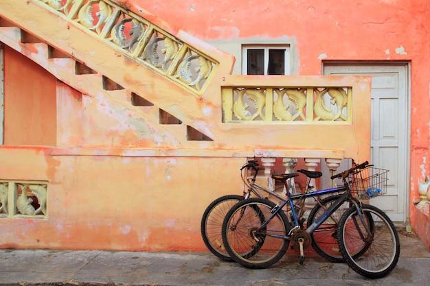 Fahrräder auf tropischer karibischer orange fassade des schmutzes