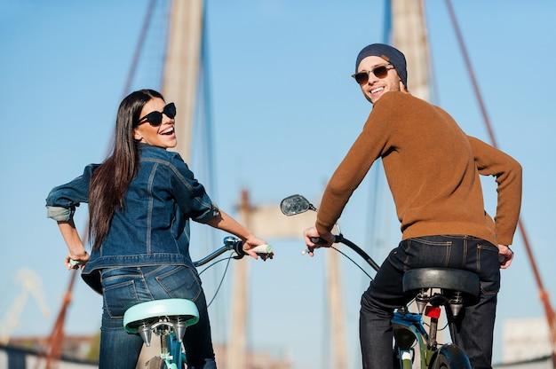 Fahrspaß genießen. rückansicht eines schönen jungen paares, das fahrrad fährt und mit einem lächeln über die schulter schaut