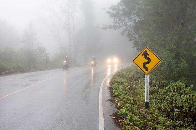 Fahrzeug fährt auf kurviger straße im dichten nebel