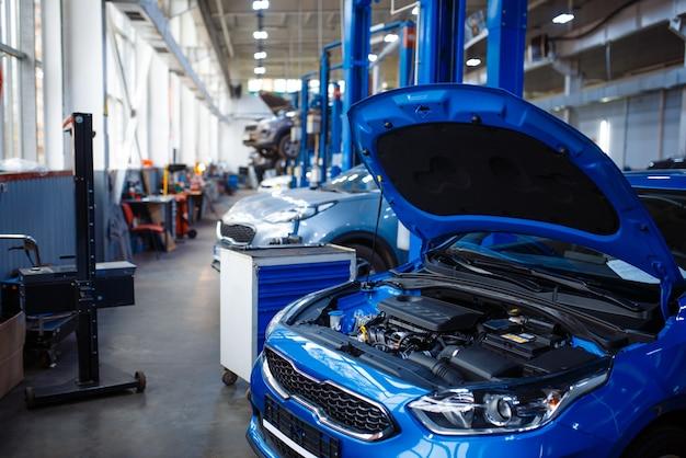 Fahrzeug mit geöffneter motorhaube am wagenheber, autotankstelle, niemand. innenraum der autowerkstatt, prüf-, diagnose- und reparaturausrüstung