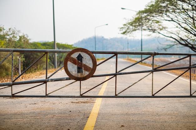 Fahrzeug sicherheitsbarriere tor und fahren sie nicht geradeaus in richtung altes verkehrszeichen auf der straße