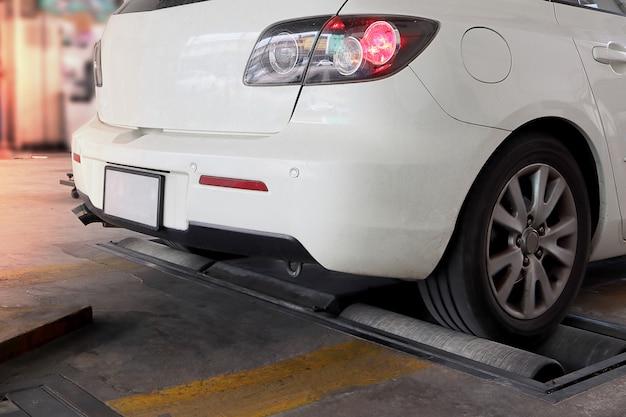Fahrzeug während rollenbremsenprüfvorrichtung, weißes farbauto.
