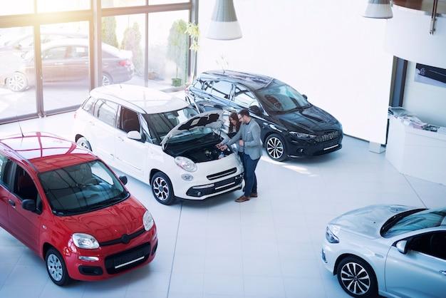 Fahrzeughändler präsentiert dem käufer im automobilausstellungsraum ein neues auto.