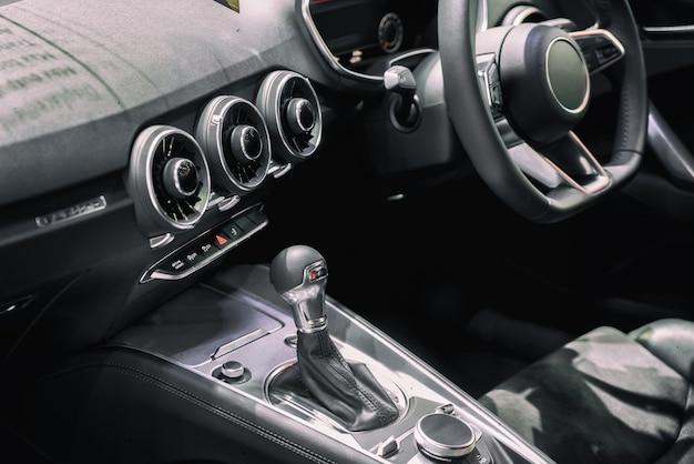 Fahrzeuginnenraum am getriebeschaltbereich. moderner autoinnenraum, gearstick radio und cup