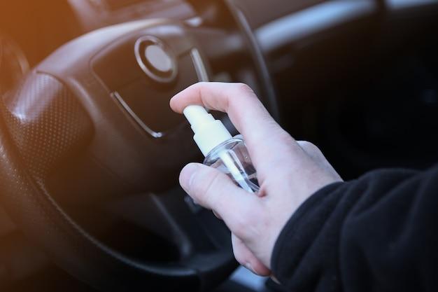 Fahrzeuginnenraum mit desinfektionsflüssigkeit reinigen. desinfektion des lenkrads und der griffe des autos. coronavirus, covid-19-schutz. desinfektion des fahrzeugs im inneren