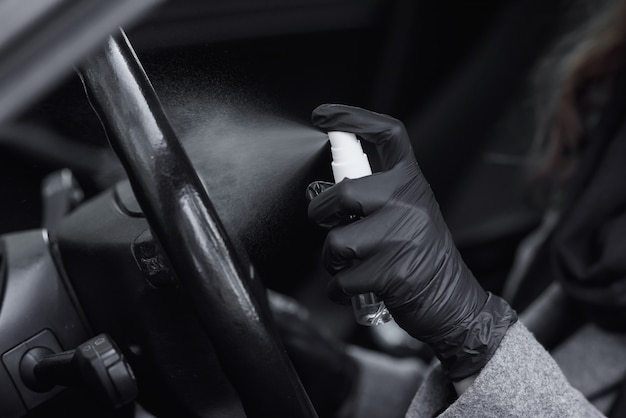 Fahrzeuginnenraum reinigen und mit desinfektionsflüssigkeit besprühen. hände in gummihandschuh desinfizieren das fahrzeug im inneren zum schutz vor viruserkrankungen