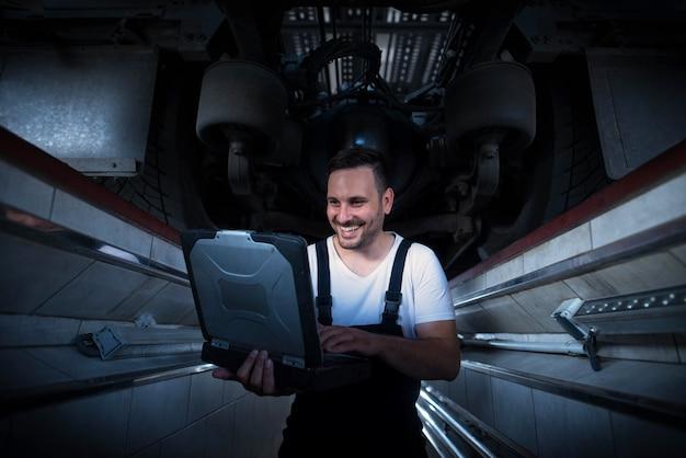 Fahrzeugmechaniker mit diagnosewerkzeug laptop, der unter dem lkw in der werkstatt arbeitet