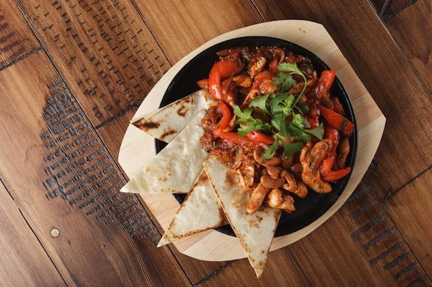 Fajitas mit hühnchen und paprika in einer pfanne