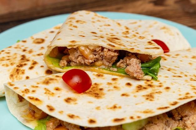Fajitos mit hackfleischgemüse in einer maistortilla auf einer blauen platte