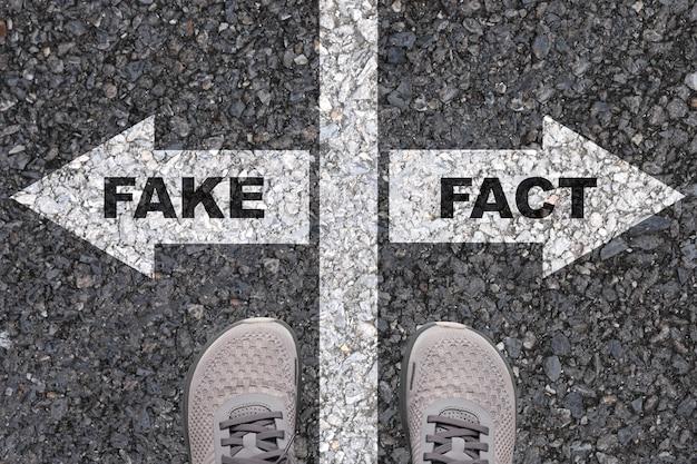 Fakt druckbildschirm auf weißem rechtspfeil zeichen auf der straße und gegenüber ist gefälschter druckbildschirm linker weißer pfeil.
