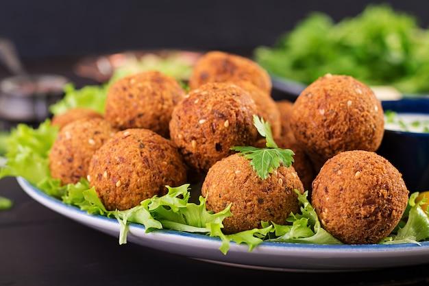 Falafel, hummus und pita. nahöstliche oder arabische gerichte auf einem dunklen tisch