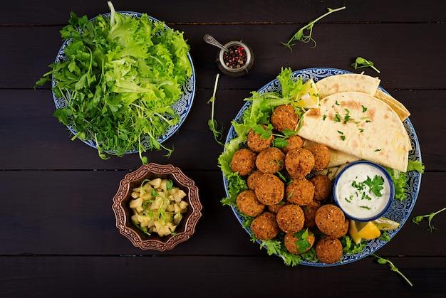 Falafel, hummus und pita. orientalische oder arabische gerichte auf dunkel