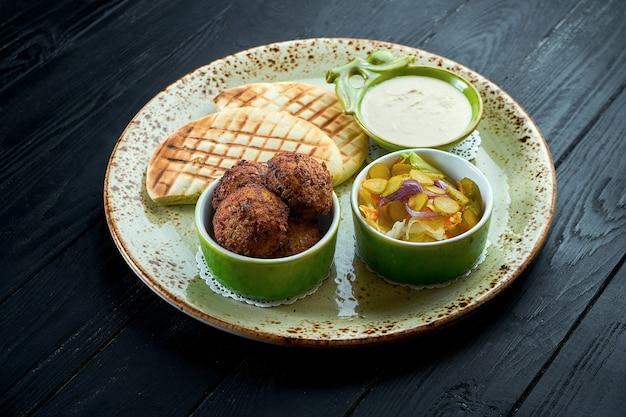 Falafel mit fladenbrot, serviert mit weißer sauce und gurken in einem grünen teller vegetarisches essen