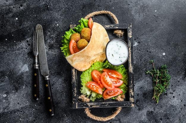 Falafel mit gemüse, sauce in fladenbrot, vegetarisches kebab-sandwich. schwarzer hintergrund. ansicht von oben.