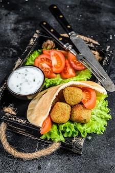 Falafel mit gemüse, sauce in fladenbrot, vegetarisches kebab-sandwich